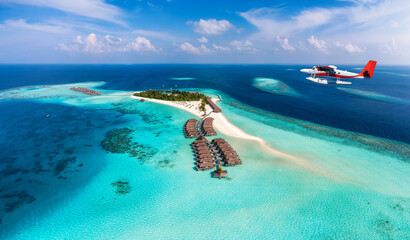 A seaplane is approaching a tropical paradise island in the Maldives with turquoise sea and sunshine