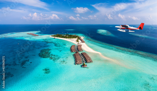 Fototapeta A seaplane is approaching a tropical paradise island in the Maldives with turquoise sea and sunshine obraz