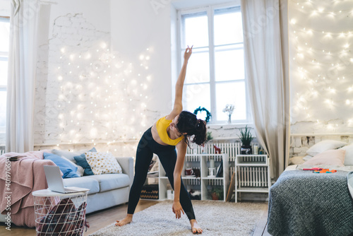 Flexible fit girl enjoying relaxation stretching exercising during morning time in cosy house interior, beautiful woman practice pilates during sportive warm up for keeping perfect body shape