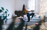 Playful hipster girl in electronic headphones feeling delight happiness during weekend time in home apartment with Christmas mood, excited female in earphones listening positive music and dancing