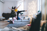 Playful hipster girl in electronic headphones having fun during weekend time in home apartment with Christmas mood, excited female in earphones listening music and dancing with expression