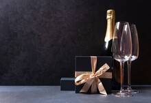 A Bottle Of Champagne, Two Glasses, A Gift Box. On A Black Background. Dark Photo.