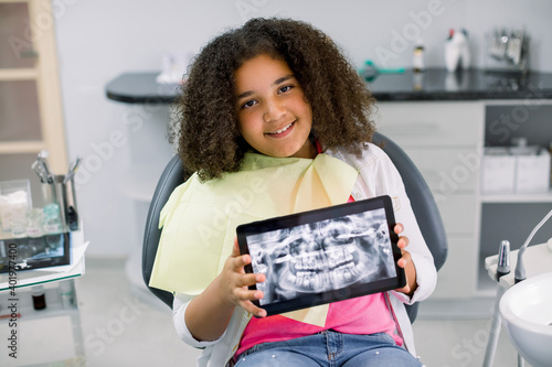 Fotografija Little smiling mixed raced girl with curly hair sitting in dental chair and looking at camera, while holding x-ray scan image of her teeth on digital tablet