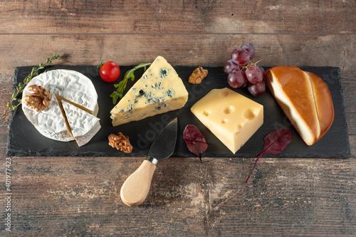 Fototapeta different cheeses laid out on long black stone Board. blue cheese Dorblu, smoked Suluguni, brie, Maasdam, cheddar, Parmesan. obraz