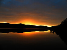 Summer Sunset In The City Of Murmansk, Late July. Dark Mountains Above The Water, Yellow Sunset, Reflection In The Water, Quiet Trees. A Beautiful View Of The Night Mountains, Murmansk Region, Russia.