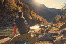 Woman Contemplating The Current Of A River Illuminated By The Sunlight Between The Mountains. Sunset In The Forest In Autumn. Ordesa Y Monte Perdido Natural Park In The Pyrenees