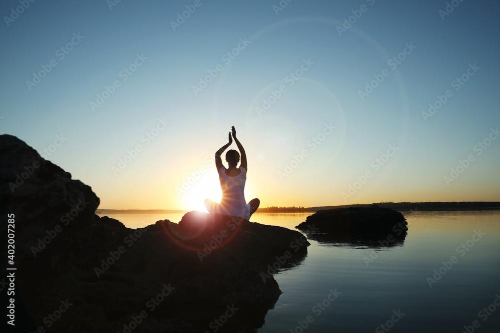 Fototapeta Woman practicing yoga near river on sunset. Healing concept