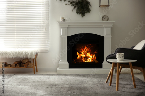 Canvas Print Bright living room interior with artificial fireplace and firewood