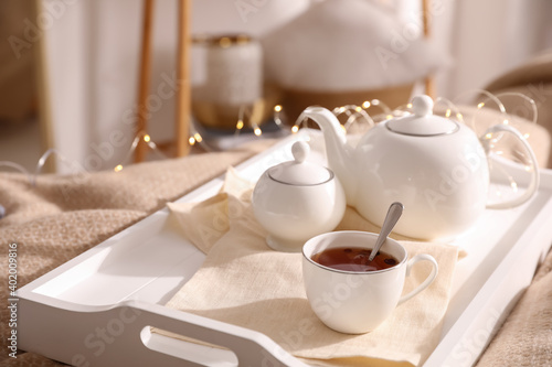 White tray with ceramic tea set on bed