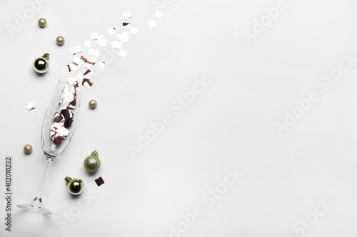 Flat lay composition with confetti, festive decor and champagne glass on light background. Space for text