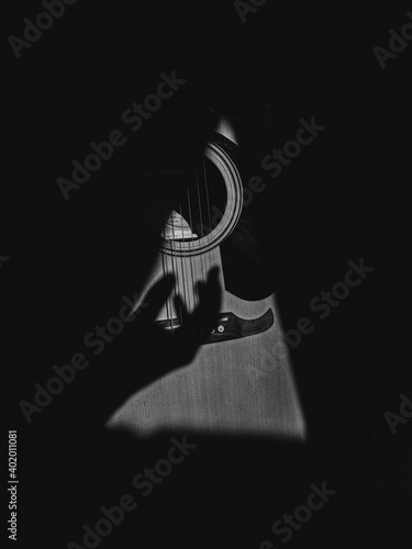 Slika na platnu A grayscale shot of a hand shadow strumming on guitar strings