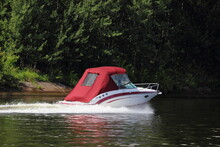 Fast Floating White Inboard Motor Boat With Closed Red Awning, Back Side View On Green Trees On Shore Background At Sunny Summer Day, Active Recreation Boating On River Canal