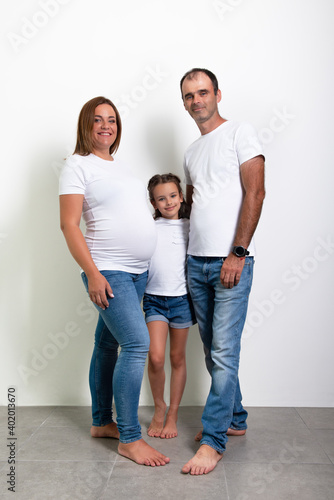 Canvas Print Pregnant mother, father and daughter posing at home. Pregnancy.