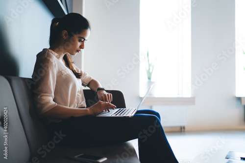 Serious businesswoman working on laptop sitting on sofa in light office