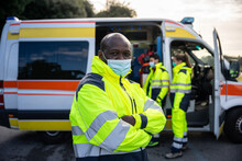 Portrait Of Young Adult Man With Arms Crossed At First Aid In Front Of His Colleagues In Ambulance At Break Time At Pandemic Time From Coronavirus, Covid-19 He Wearing Face Mask And Uniform Work