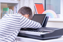 Sad Frustrated Teen Boy Has Difficulty Learning To Play Piano. Kid Using Digital Tablet To Watch Video Lesson At Home. Online Learning Difficulties