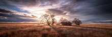 An Old Farmhouse On The Eastern Plains Of Colorado In A Rural Setting At Sunset. The Sky Is Dramatic With Wispy Clouds. The Old House If Falling Apart And Abandoned.
