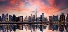 Stunning Panoramic View Of The Dubai Skyline At Sunset With Buildings And Skyscrapers Reflected On A Silky Smooth Water Flowing In The Foreground. Dubai, United Arab Emirates.