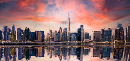 Obraz Stunning panoramic view of the Dubai skyline at sunset with buildings and skyscrapers reflected on a silky smooth water flowing in the foreground. Dubai, United Arab Emirates. - fototapety do salonu