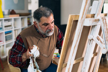Senior Man Painting Picture At Home