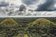 Chocolate Hills With A Group Of Clouds In The Sky