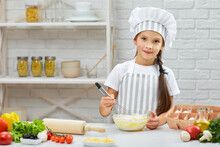 Little Child Girl In Cap And An Apron Kneads With Corolla The Dough In The Kitchen. MIxing Baking Ingredients