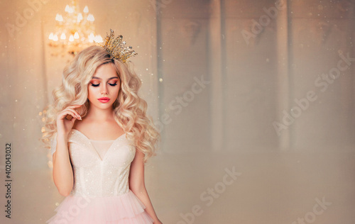 Portrait capricious fantasy princess girl. Blond lond hair gold crown. Fairy tale lady woman in vintage dress. White room lamp chandelier. Bored fashion model queen. free space for text wide screen.