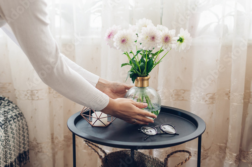 Fotografering Woman puts vase with flowers dahlias on table