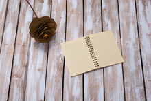 A Top View Of A Brown Flower And An Open Notebook On A Worn Wood Plank Background