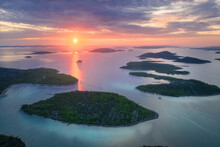 Aerial View Of Beautiful Small Islands In Adriatic Sea At Sunset In Summer In Croatia. Top View Of Blue Water, Green Trees On The Mountains, Colorful Sky With Clouds And Orange Sun. Tropical Landscape