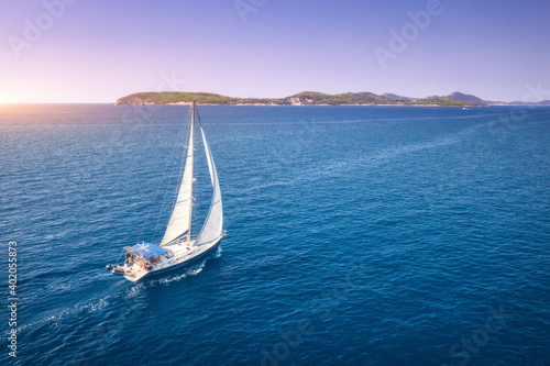 Obraz Aerial view of beautiful white sailboat in blue sea at bright sunny summer evening. Adriatic sea in Croatia. Landscape with yacht, mountains, transparent blue water, sky at sunset. Top view of boat - fototapety do salonu