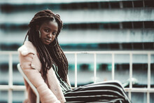 A True Tilt-shift Portrait With A Selective Focus On The Part Of The Face And Hair Of A Dazzling Young Black Woman With A Dreadlock Sitting Outdoors On The Balcony, With A Copy Space Place On The Righ