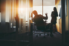 Wide-angel View Through The Door Of A Job Interview In An Office Boardroom: A Bossy Man Entrepreneur On An Armchair Is Questioning A Female Job Seeker, Asking About Her Experience Actively Gesturing