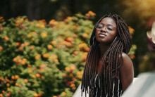 A Ravishing Young Black Female With Dreadlocks And Eyeglasses In The Public Park With A Bush With Flowers In The Defocused Background; A Portrait Of A Dazzling African Woman With Dreads And In Glasses