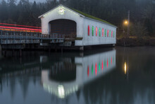 Old Vintage Wooden Covered Bridge Over A River With Red And Green Christmas Lights In The Windows.