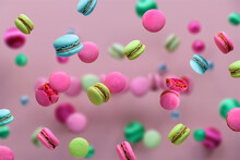 Levitation Of Macaroons, Creative Food Concept. Bold Vibrant Pink, Mint Green, Mint Blue And Magenta Colors. Flying Macaroons, Disco Balls And Decorative Metallic Balls On Pink Background.