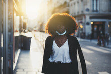 A Portrait Of A Young Gorgeous Black Girl With A Lowered Antivirus Mask On Her Face, Standing On The Street Lit By A Bright Evening Sun Near The Crosswalk With A Jacket Thrown Over The Shoulders