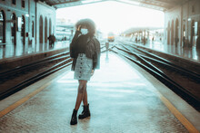 Svelte Young Black Female In A Casual Outfit And Virus Protective Mask On The Face Is Fixing Her Curly Hair While Standing On A Platform Indoors Of A Covered Railway Station Depot, Waiting For A Train