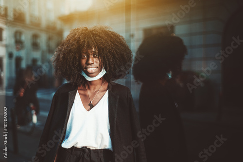 Obraz Portrait of a young beautiful cheerful black woman in a lowered virus protective mask, with a coat thrown over her shoulders, she's on the street leaning against a glass wall facade reflecting her - fototapety do salonu