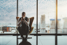 A Portrait Of A Man Entrepreneur In A State Of Worry And Dismay Sitting On An Armchair In Front Of The Window Of A Luxury Office High-rise And Thinking About How To Solve Recent Business Issues