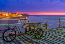 A Beautiful View Of The Sunset With Pink And Blue Clouds Over A Cart Bicycle Standing On The Bridge