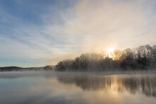 Fog Rises On The Water Of Lake Lanier In Georgia At Sunrise Under A Blue And Orange Sky