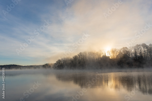 Fotografie, Tablou Fog rises on the water of Lake Lanier in Georgia at sunrise under a blue and ora