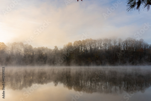 Tablou Canvas Fog rises on the water at sunrise on Lake Lanier in Georgia with a reflection of