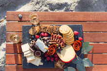 Top View Of A Grazing Board Of Charcuterie, Crackers, Berries, And Cheeses With A Glass Of Champagne On A Wood Table Set On The Beach