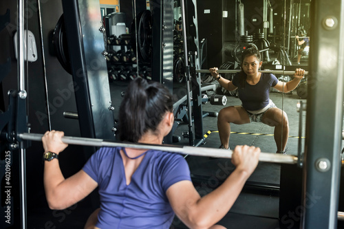 Papel de parede A lazer focused young woman does intense back squats on a smith machine while looking at mirror to check her form
