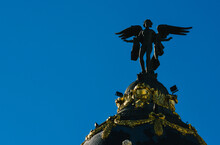 A Low Angle Shot Of Winged Victory Statue At The Top Of The Metropolis Building In Madrid