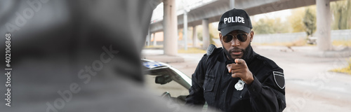 Fotografia serious african american police officer pointing with finger at blurred hooded offender on foreground on urban street, banner