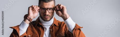 Obraz Serious stylish man adjusting eyeglasses and looking at camera isolated on grey, banner - fototapety do salonu