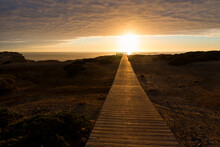 Wooden Boardwalk At Sunset, Coastal Landscape Carrapateira West Algarve. Cloudy Sky